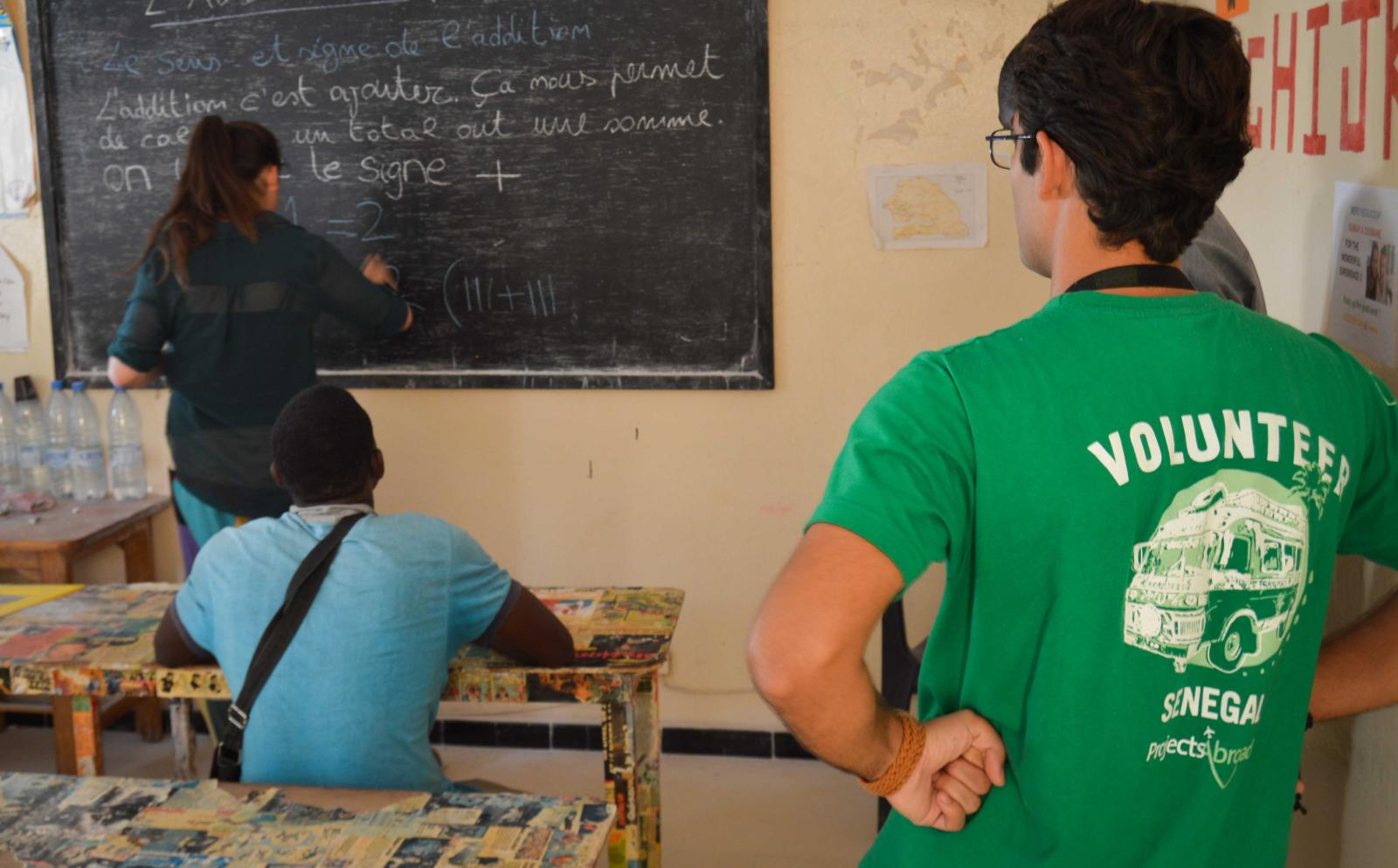 Projects Abroad volunteers provide a local business owner with math lessons in Senegal